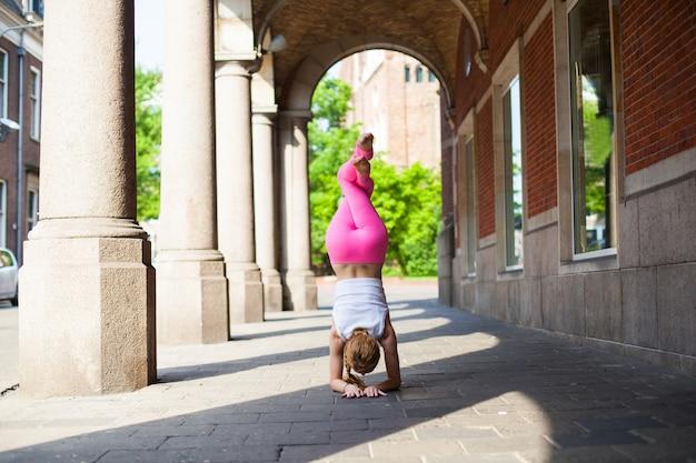 Menina de manhã fazendo yoga na cidade