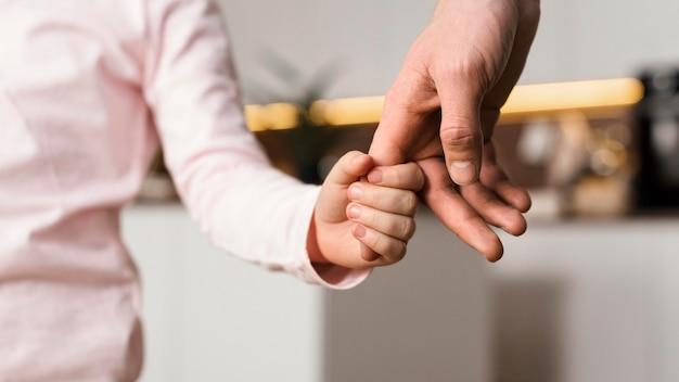 Menina de mãos dadas com o pai
