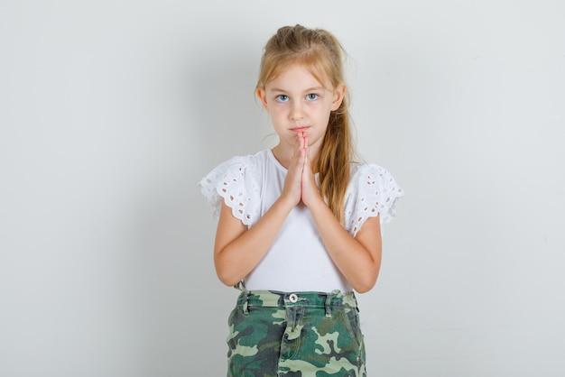 Menina de mãos dadas em gesto de oração em camiseta branca