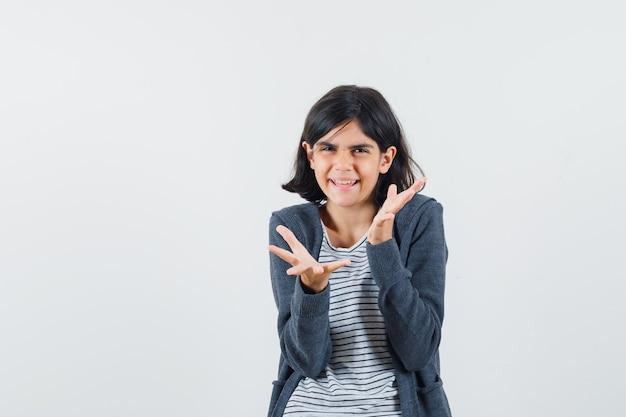 Menina de mãos dadas em um gesto perplexo na camiseta, jaqueta e parecendo brincalhão.