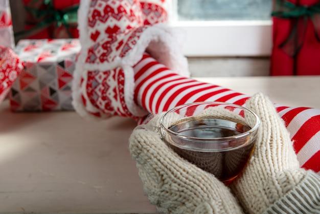 Menina de meias, desfrutando de um inverno, bebendo uma xícara de chá