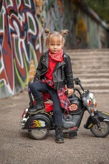 Menina de moda fofa e descolada com jaqueta de couro andando de moto