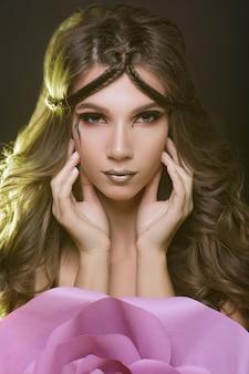 Menina de modelo de moda linda com uma maquiagem criativa.