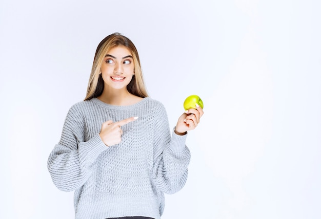 Menina de moletom cinza segurando a maçã verde na mão.