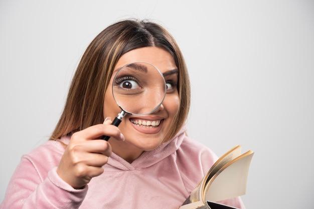 Menina de moletom rosa colocando uma lupa no olho e olhando através dela.