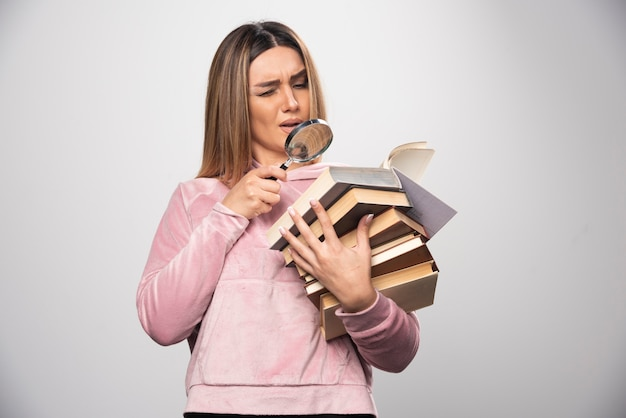 Menina de moletom rosa segurando um estoque de livros e tentando ler o de cima com uma lupa.