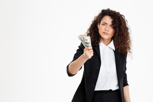 Menina de negócios seriamente encaracolado segurando o dinheiro