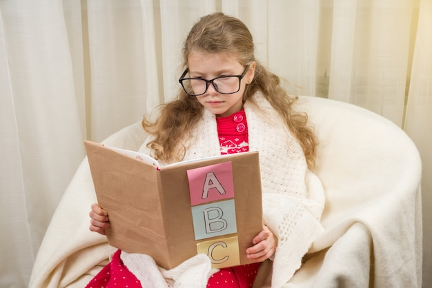 Menina de óculos aprende a ler um livro
