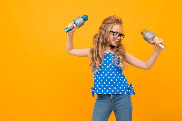 Menina de óculos balançando as mãos com microfones