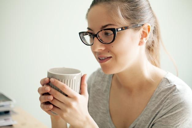 Menina de óculos, bebendo café