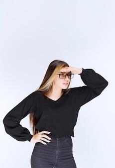Menina de óculos, colocando a mão na testa para observar.