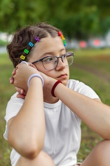 Menina de óculos com clipes de cabelo coloridos com arco-íris ao ar livre, tema lgbt, orgulho