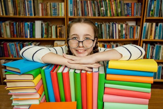 Menina de óculos com livros na biblioteca