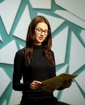 Menina de óculos com um jornal