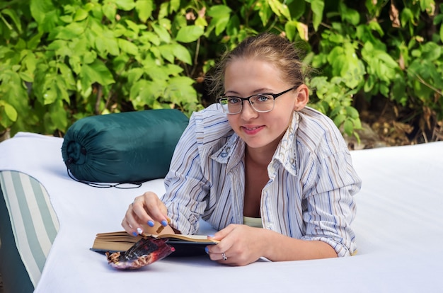 Menina de óculos com um livro deitada em um colchão de ar na floresta