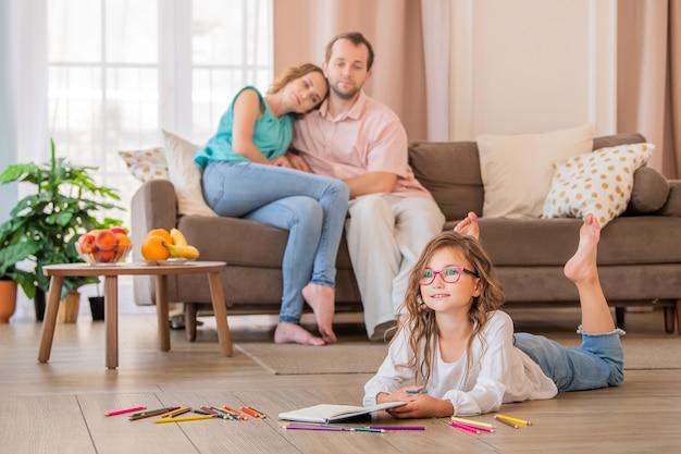 Menina de óculos desenha com giz de cera, deitado no chão da casa. pais felizes estão sentados no fundo.