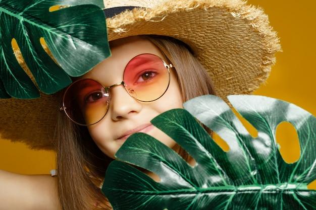 Menina de óculos e um chapéu de palha em um fundo amarelo no estúdio