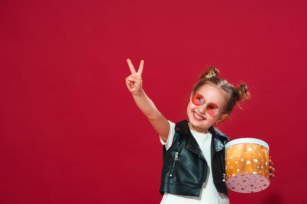 Menina de óculos escuros com caixa de presente mostrando o sinal v