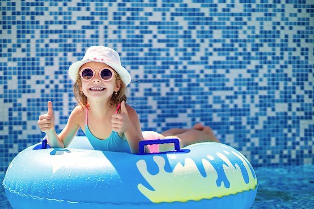 Menina de óculos escuros e chapéu com unicórnio no anel amarelo inflável na piscina do resort de luxo em férias de verão na ilha de praia tropical.
