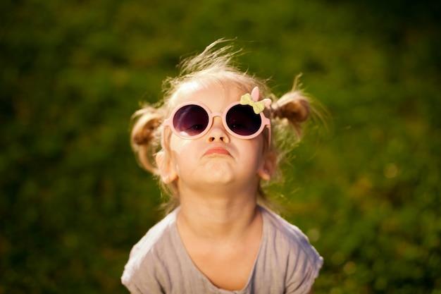 Menina de óculos escuros posando no parque