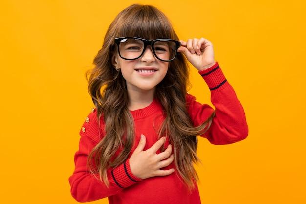 Menina de óculos estrabismo em uma parede laranja