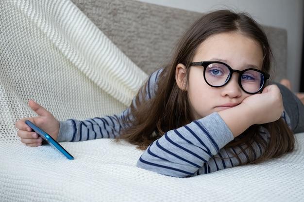 Menina de óculos estudando no telefone e deitada no sofá