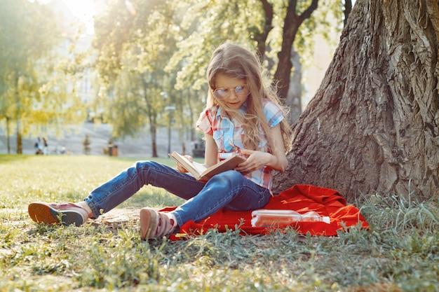 Menina de óculos lendo livro no parque, na grama perto da árvore