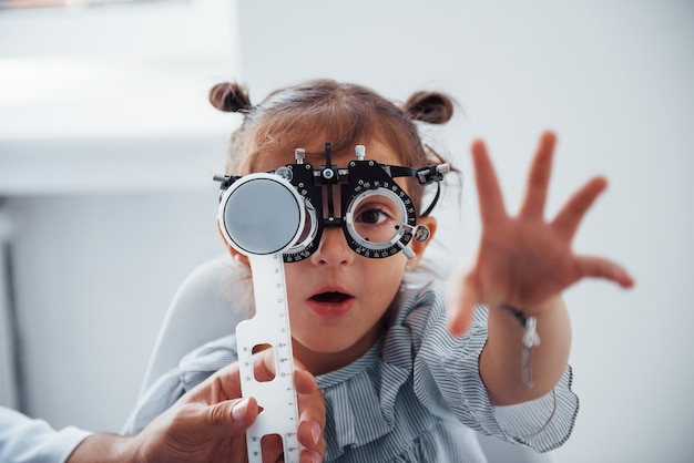 Menina de óculos na clínica de oftalmologia tem teste de visão.