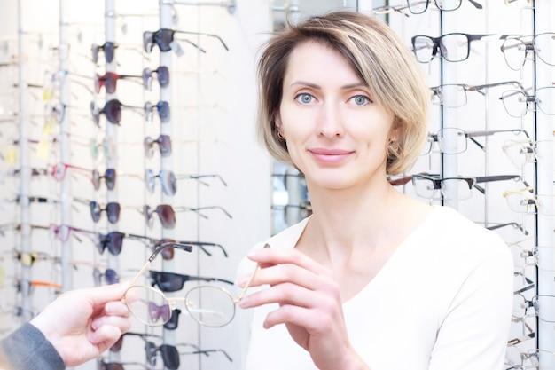 Menina de óculos para a visão. tentando óculos em uma loja de óptica.