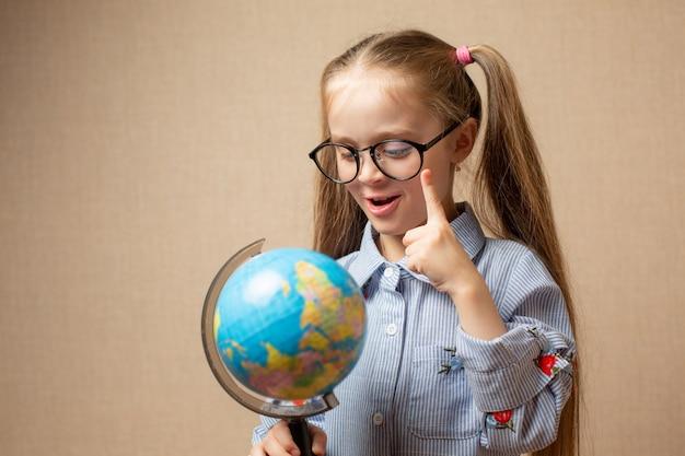 Menina de óculos, segurando o globo