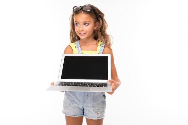 Menina de óculos, segurando um computador nas mãos com maquete na parede azul clara