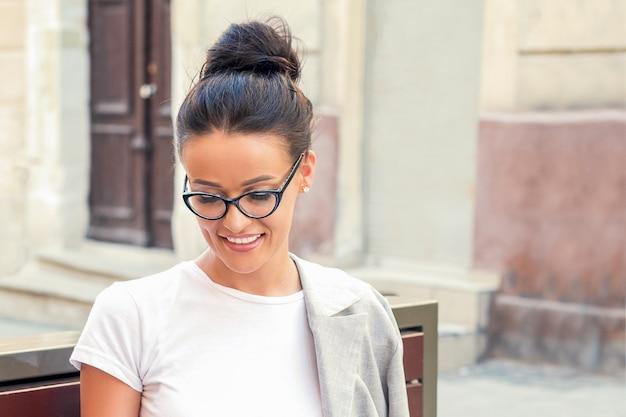 Menina de óculos, sentada no banco.