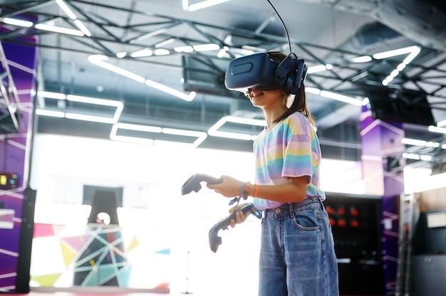 Menina de óculos vr tem joysticks nas mãos. criança jogando videogame 3d no centro de entretenimento. crianças se divertindo, criança passando o fim de semana no parquinho, infância feliz