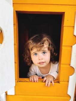 Menina de olhos azuis brincando na casa de bonecas.