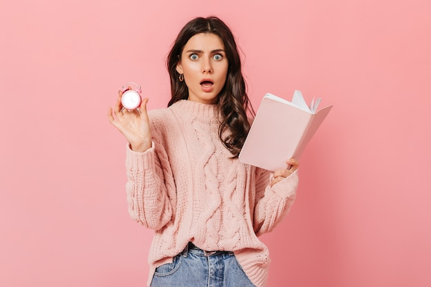 Menina de olhos azuis em estado de choque olha para a câmera no fundo rosa. senhora de camisola elegante, posando com despertador e diário.