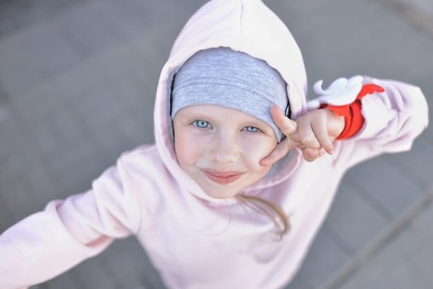 Menina de olhos azuis em roupas quentes e capuz olha para cima e cumprimenta com gestos.