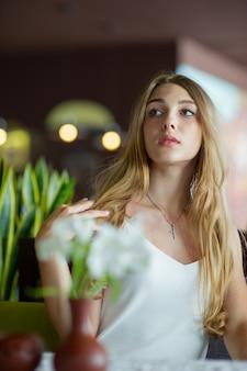 Menina de olhos azuis, sentada no café urbano. mulher com penteado ondulado marrom. conceito de estilo de vida.