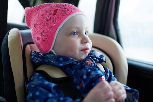 Menina de olhos azuis, sentado em uma cadeira de criança no banco de trás do carro na janela