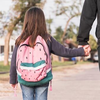 Menina de pai andando de colheita para a escola