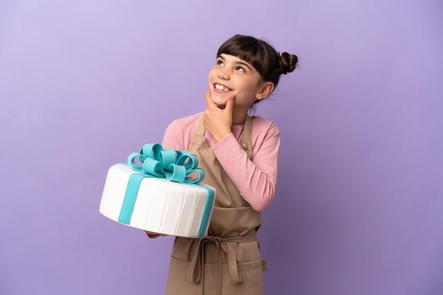 Menina de pastelaria segurando um grande bolo isolado em roxo olhando para o lado e sorrindo