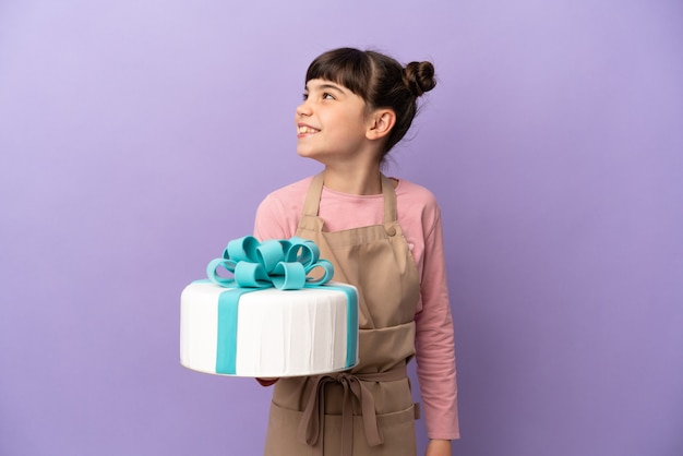Menina de pastelaria segurando um grande bolo isolado na parede roxa olhando para o lado e sorrindo