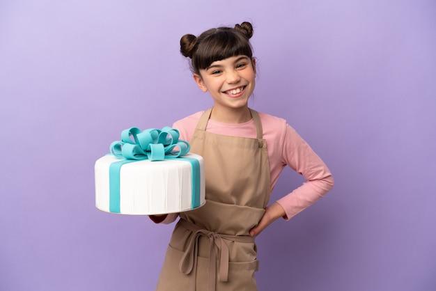 Menina de pastelaria segurando um grande bolo isolado na parede roxa, posando com os braços na cintura e sorrindo