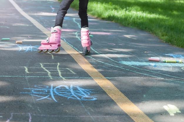 Menina de patins rosa no verão, ao ar livre.