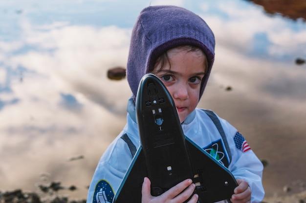 Menina de pé com brinquedo de nave espacial