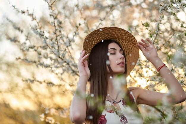 Menina de pé de chapéu no parque no pôr do sol de noite. viajante de mulher elegante no jardim primavera.