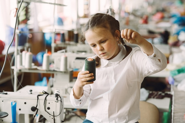 Menina de pé na fábrica com um fio