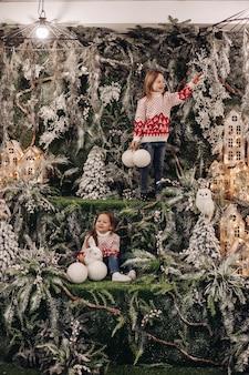 Menina de pé no andar superior da decoração de natal