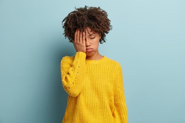 Menina de pele escura cansada, com excesso de trabalho, expressão sonolenta, aparência sombria, cobre o rosto com as mãos, tem os olhos fechados, ofega de cansaço, usa modelos de roupas amarelas sobre parede azul, fadiga após a festa