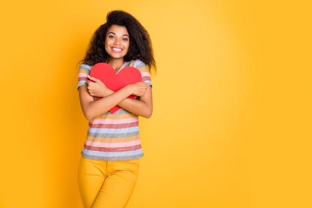 Menina de pele escura em camiseta listrada abraça cartão de dia dos namorados