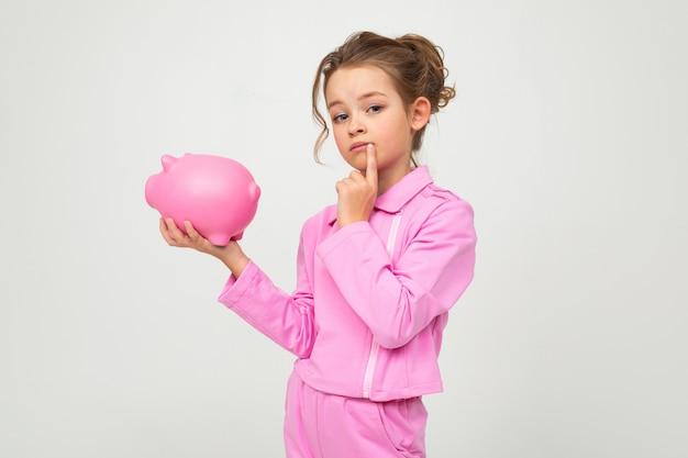 Menina de pensamento em um terno rosa, segurando um pote de dinheiro em uma parede branca com espaço em branco